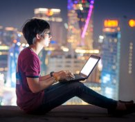 Boy using a computer with city skyscape in the background